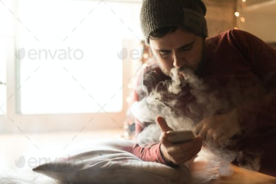 Man using a vaper and smartphone