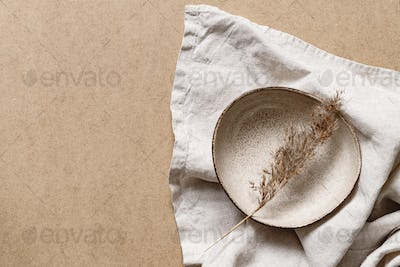 Minimalist ceramic bowl with dry plant over kraft paper background.
