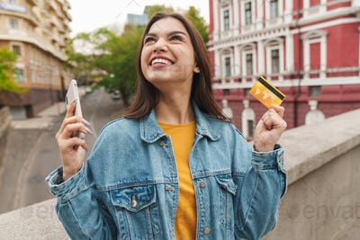 Image of woman holding credit card and mobile phone while walking