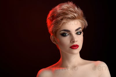 Beautiful young blonde red lipped woman posing in artistic red lighting