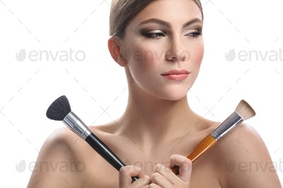 Gorgeous young woman holding makeup brushes isolated on white