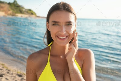 Girl Applying Sun Cream On Face For UV-Protection At Seaside