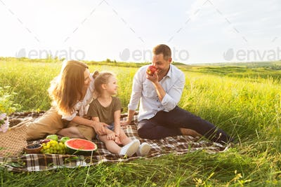Happy family playing with fruits on a picnic outdoors