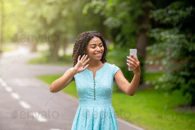 Cheerful black woman communicating online with family or friends on smartphone at park