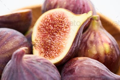 Close up View of Ripe Delicious Fig Half in Wooden Bowl on White Background