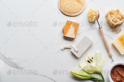 Natural Clay Mask, Soap Pieces, Body Brush, Pumice Stone And Loofah Near Fresh Flower on Surface