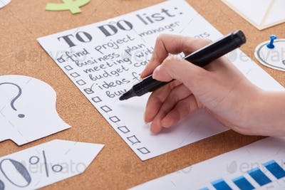 Cropped View of Woman Writing With Black Highlighter on to do List on Cork Board