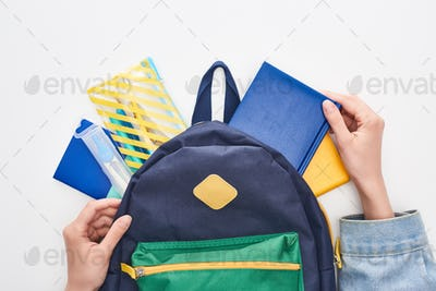 Blue Schoolbag With Notepad And Pencil Case in Hands of Schoolgirl Isolated on White