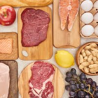 Assorted Meat, Poultry, Fish, Eggs, Fruits, Vegetables, Cheese And Baguette on Wooden Cutting Boards
