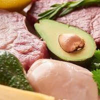 Close up View of Half of Avocado Between Raw Meat And Poultry With Rosemary And Parsley Twigs