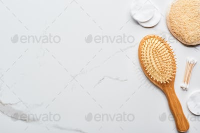 Top View of Cotton Pads And Swabs Near Hair Brush And Face Sponge on Marble Surface