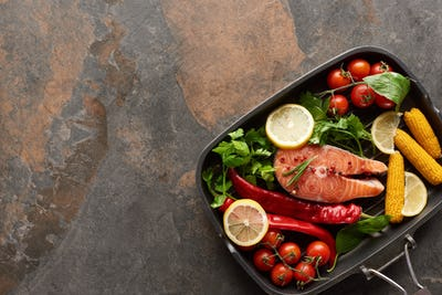 Top View of Uncooked Salmon With Vegetables, Lemon And Herbs in Grill Pan