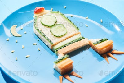 Close up View of Plate With Rocket Made of Food For Childrens Breakfast on Blue Background