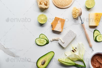 Natural Soap Pieces, Body Brush, Loofah And Pumice Stone Near Fresh Flower, Lime, Cucumber, Avocado