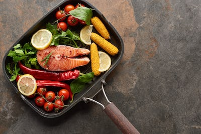 Top View of Raw Salmon With Vegetables, Lemon And Herbs in Grill Pan