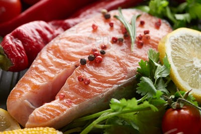 Close up View of Raw Salmon Steak With Spices, Vegetables And Greenery