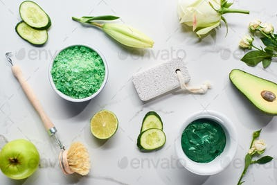 Natural Clay Mask, Brush, Pumice Stone Near Apple, Lime, Cucumber, Avocado And Flowers on Surface