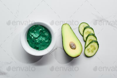 Top View of Natural Clay Mask Near Fresh Avocado Half And Cucumber Slices on Marble Background