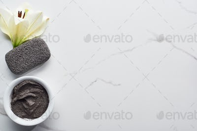 Top View of Natural Clay Mask And Pumice Stone Near Fresh Flower on Marble Surface