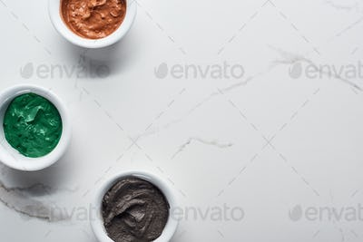 Top View of Cups With Diverse Natural Beauty Products on Marble Surface