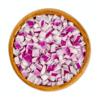 Diced red onions, cut onion cubes in a wooden bowl