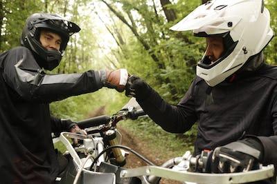 Friends enjoying motorcycling in forest