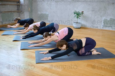 Group of women doing child pose in hall