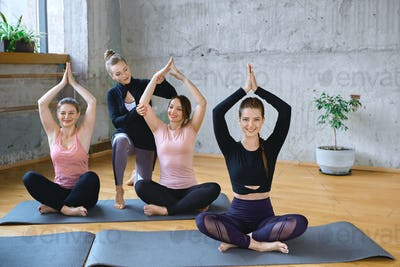 Trainer helping women practicing meditation in hall