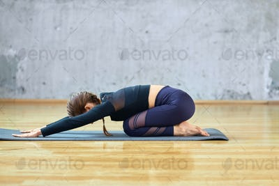 Fit woman practicing child pose in hall