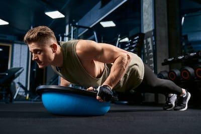 Muscular man doing push ups using balance ball