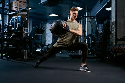 Sportsman doing lunges using ball