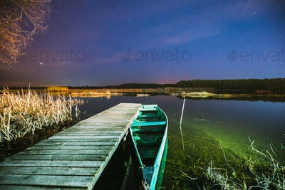 Real Night Sky Stars Above Old Pier With Moored Wooden Fishing Boat. Natural Starry Sky And
