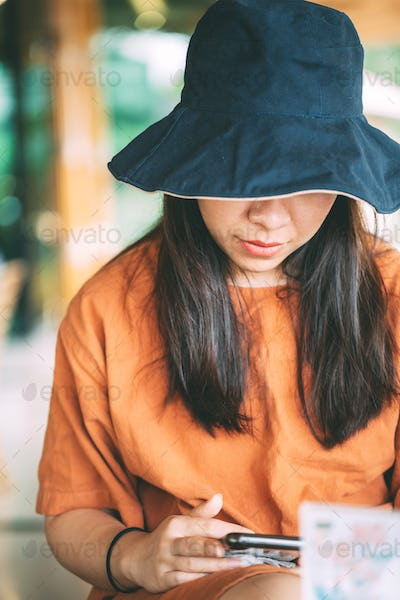 Asian girl sitting in coffee shop playing mobile phone for social media on vacation time, girl