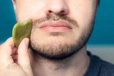 Bearded man is using jade face roller