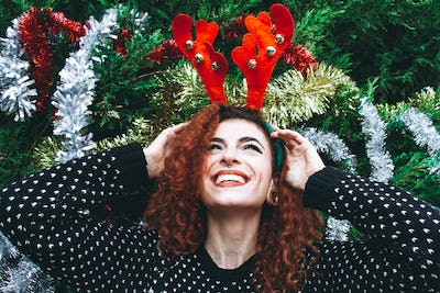 Young happy redhead woman near a christmas tree on holidays