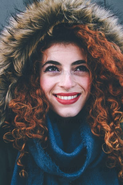 Beautiful portrait of an attractive redhead woman wearing winter clothes