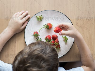 Little boy eats fresh organic strawberry with relish
