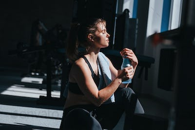 Shadows and natural lighting. Photo of gorgeous blonde woman in the gym at her weekend time