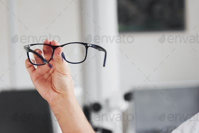 Focused photo. Woman hand holds the blue eyeglasses in the doctor cabinet