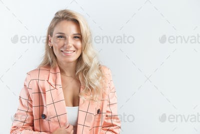 Blonde smiling woman with curly hairstyle dressed in a formal pink jacket on white background.