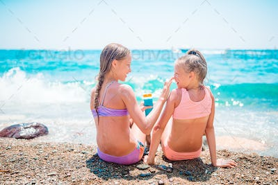 UV protection. Sister puts sunscreen on her little sister's nose
