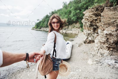 Portrait of happy young woman in hat holding man by hand and going to the boat on the lake