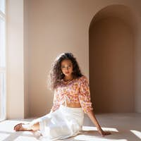 Mulatto female model posing on floor under sunlight