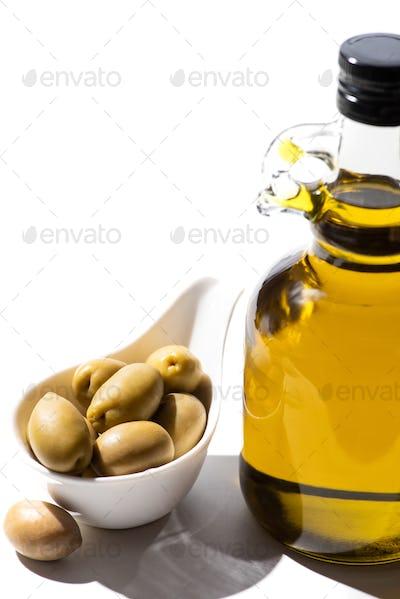 Olive Oil in Bottle Near Green Olives in Gravy Boat on White Background