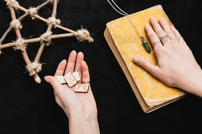 Top View of Witch Holding Runes And Putting Hand on Aged Book Near Pentagram on Black