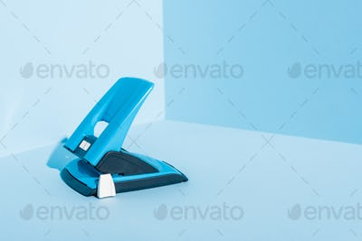 Blue Plastic Hole Puncher on Blue Background