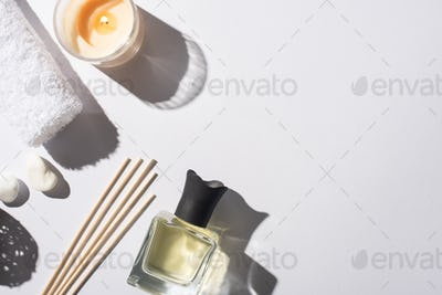 Aroma Sticks With Perfume in Bottle Near Cotton Towel, Stones And Candle on White Background