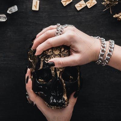 Close up of Woman Holding Skull Near Runes And Crystals on Black