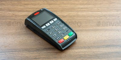 Payment machine, POS terminal on wooden background.