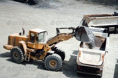 Industrial heavy duty large wheel loader moving gravel and loading dumper trucks
